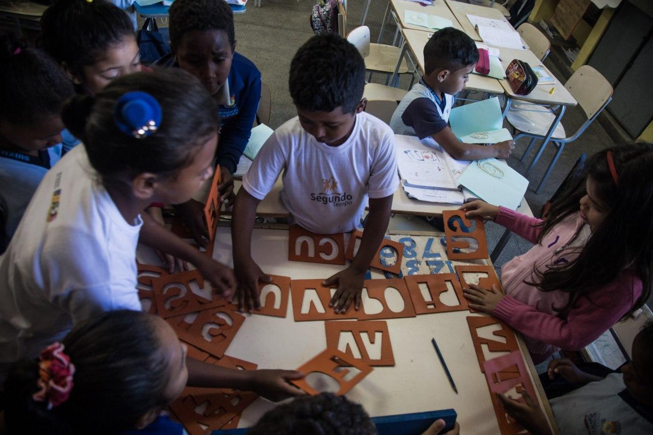 Crianças manuseiam peças de papelão vazadas com a forma de letras e sílabas sobre uma mesa escolar.