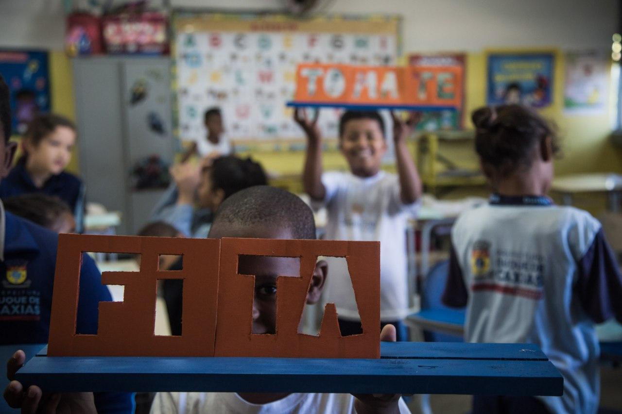 Aluno segura peças que formam a palavra FITA. Atrás dele, outro estudante forma a palavra TOMATE.