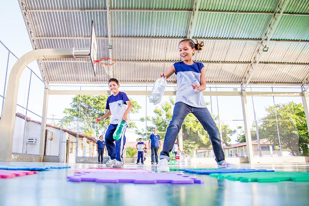 Dois estudantes jogam uma versão ampliada de jogo da velha na quadra da escola.