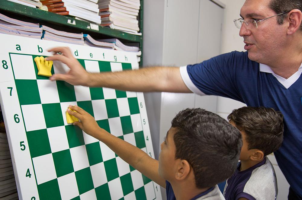 Professor mostra tabuleiro magnético de xadrez para estudantes.
