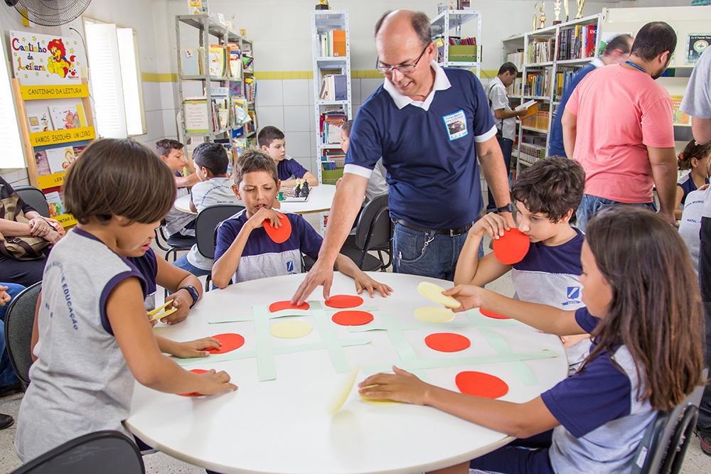 Grupo de cinco crianças jogam jogo da velha ampliado sobre a mesa, com pedaços de cartolina recortados.