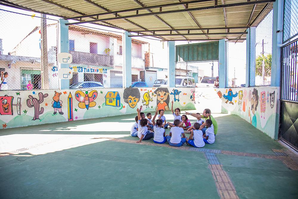 Um grupo de crianças e o professor de educação física sentados em círculo no pátio da escola.