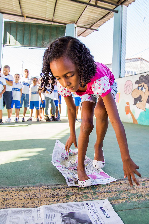 Garota pisa sobre folhas de jornal em pátio da escola.