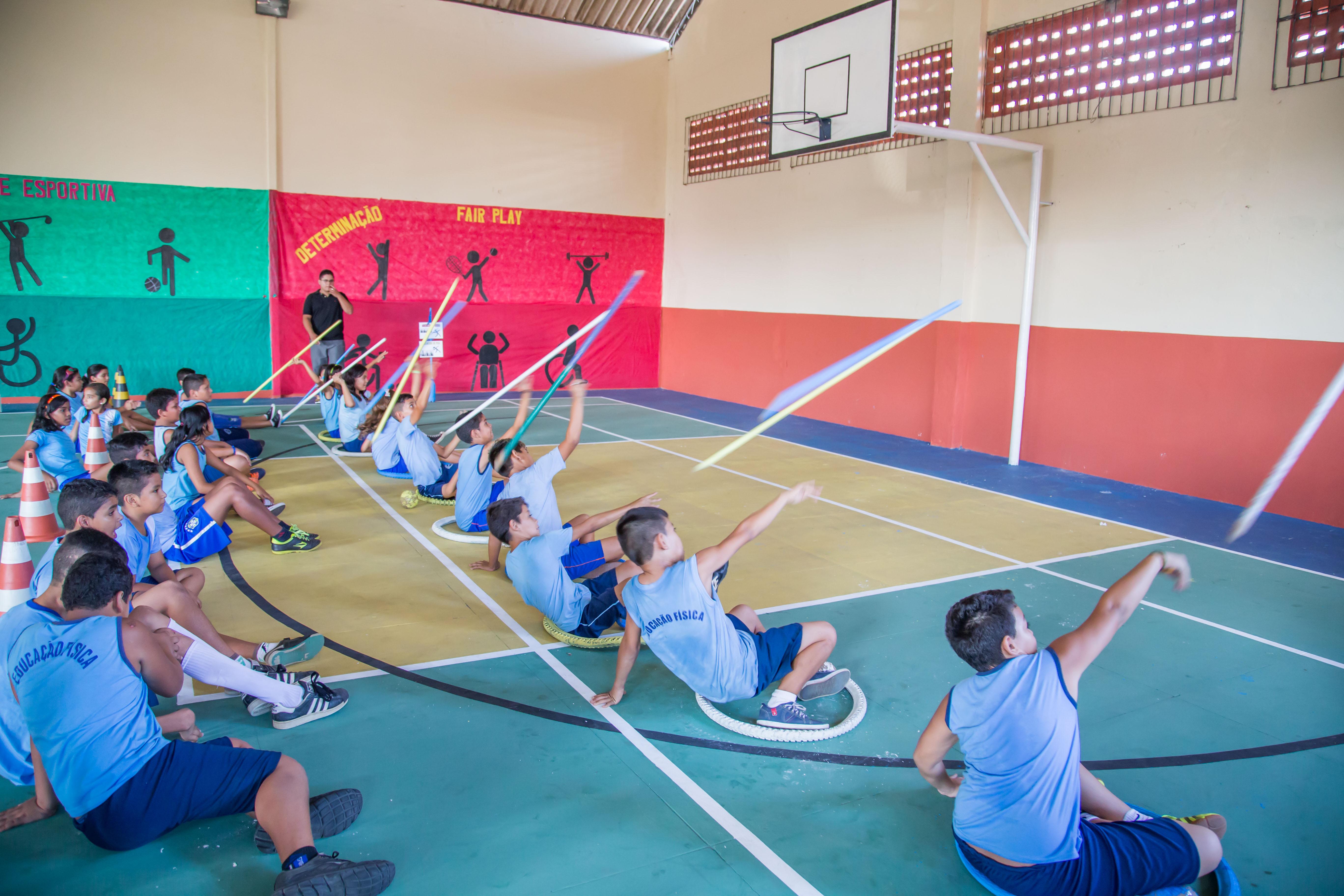 Um grupo de alunos está sentado em uma quadra de esportes, cada um dentro de um bambolê. Cada aluno segura um cabo de vassoura com a mão sobre a cabeça.
