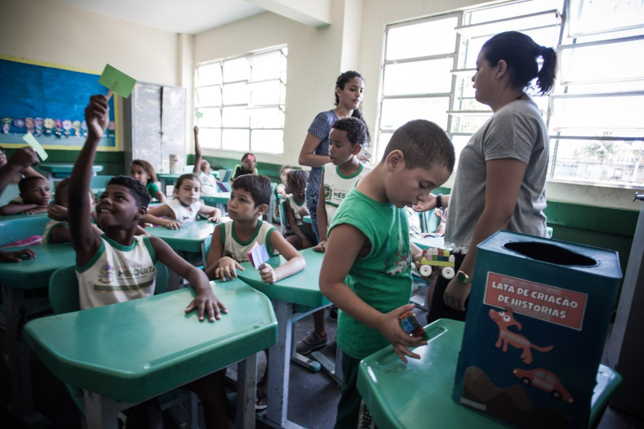 Garoto cola figuras na lata na frente da sala. Atrás dele, os demais estudantes levantam placas coloridas.