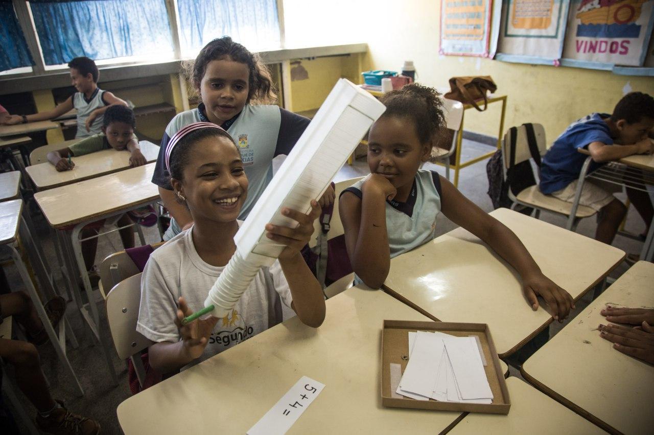 Duas alunas estão sentadas lado a lado na sala de aula manuseando a Máquina de somar. Uma terceira menina observa atrás delas.