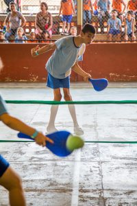 Dois garotos jogam tênis juntos com raquetes feitas de material reutilizável pintado de azul.