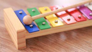 Um xilofone com teclas coloridas sobre uma mesa de madeira.