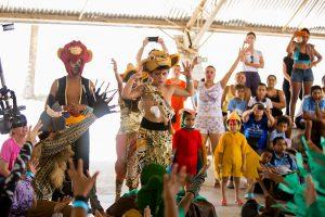 Um grupo de estudantes interpreta cena do musical O Rei Leão. Eles estão usando fantasias de diversos animais como macacos, lagartos, pássaros, entre outros.