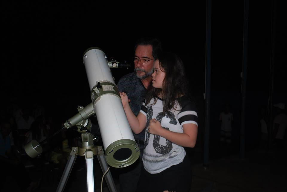 Professor de química ajuda estudante com síndrome de down a manusear o telescópio durante observação astronômica.