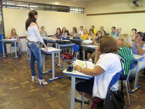 Professores do colégio assistem à fala de diretora em sala de aula.