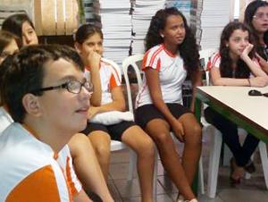 Alunos sentados em cadeiras de plástico assistem à um filme na escola.