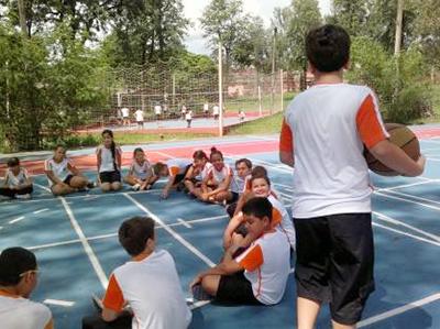 Um grupo de estudantes está sentado em círculo em uma quadra. Um aluno segura uma bola e anda em volta do círculo.