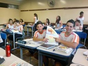Dois estudantes sentados lado a lado seguram um mapa.