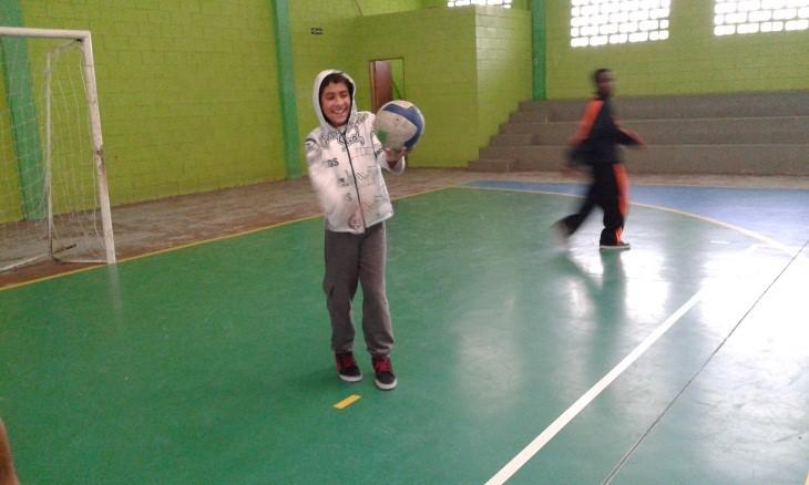 Caio, sorridente em uma quadra de esportes, faz um movimento de manchete em uma bola de vôlei