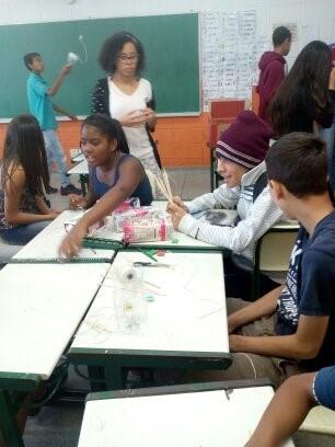 Um grupo de estudantes está sentado em carteiras colocadas uma de frente para a outra fazendo uma atividade em grupo.