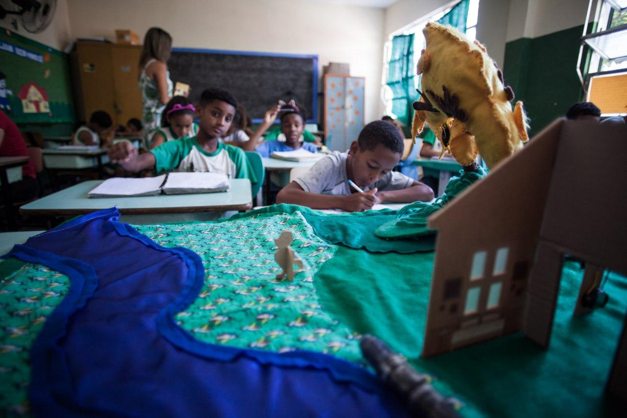 Com o Tapete de histórias interativo na frente da sala, alunos sentados em suas carteiras escrevem em seus cadernos.