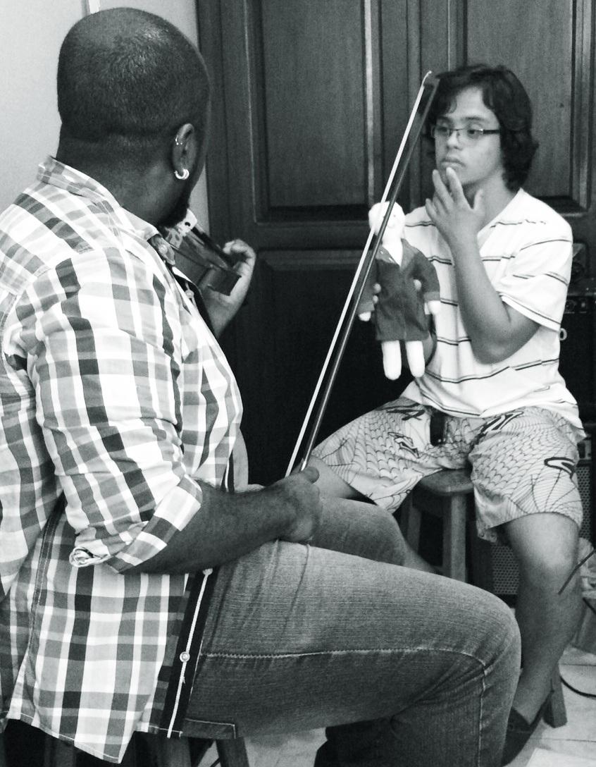 Gabriel ensaia com músico. Ele está sentado diante de um homem que toca um violino. Gabriel segura um boneco com uma das mãos.