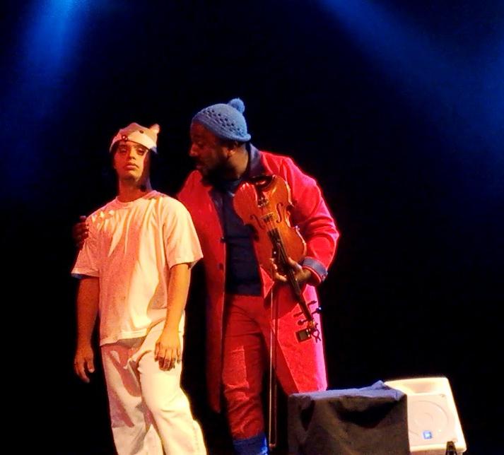 Dois atores contracenam no palco. Gabriel está de pé, vestido com roupas brancas. Ao seu lado, tocando em seu ombro, um músico seguro um violino enquanto conversa com ele.