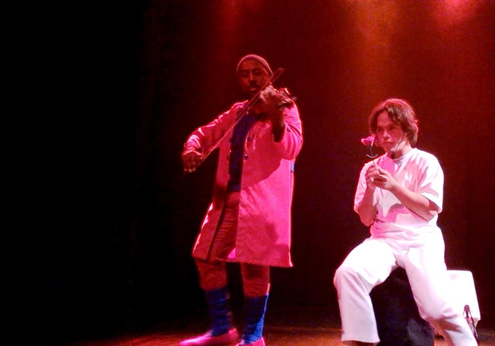 Dois atores contracenam no palco. Gabriel está sentado em um caixote, segurando uma rosa. Ao lado dele, um músico de pé toca um violino.