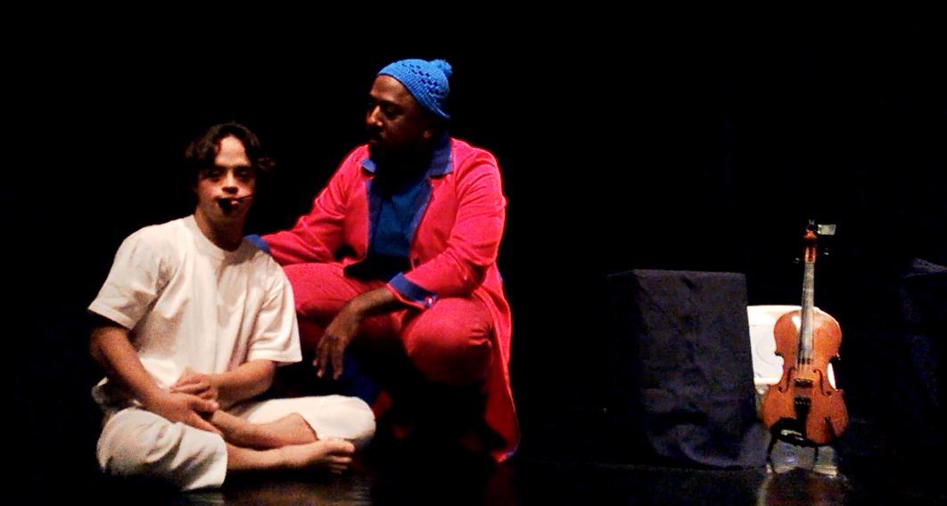 Dois atores contracenam no palco. Gabriel está sentado, de pernas cruzadas. Seu companheiro de cena usa roupas vermelhas e está agachado ao seu lado. Há um violino em pé do outro lado do palco.