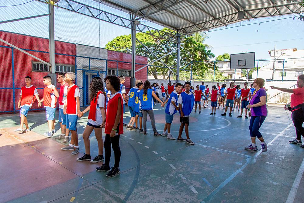 Estudantes de mãos dadas se posicionam em quadra como peças de uma mesa de pebolim. Eles estão divididos em dois times, caracterizados pelos coletes azuis e vermelhos. Há duas fileiras de cada time intercaladas.