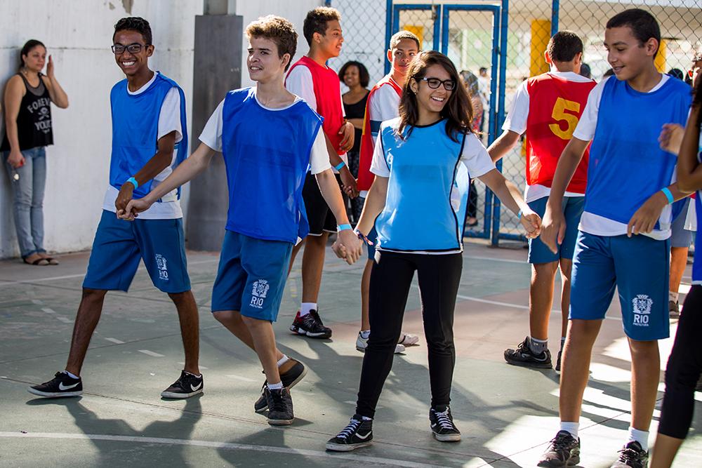 Quatro adolescentes usando coletes azuis e de mãos dadas em linha comemoram.