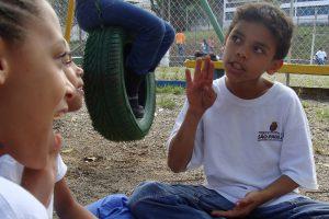 Três crianças gesticulam em Língua brasileira de sinais. Elas estão em um pátio escolar e usam uniformes.