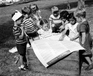 Um grupo de 8 crianças ao redor de um banner grande onde está impressa a Declaração. A foto é em preto e branco, mostrando ser antiga.