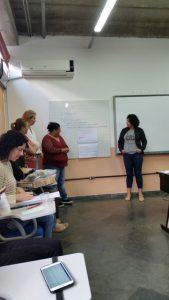 Grupo de educadoras reunido em uma sala de aula. Parte delas está sentada, outra parte está de pé diante de todas.