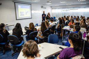Uma sala cheia de pessoas sentadas em carteiras, diante de um telão. Na frente, dois educadores falam.