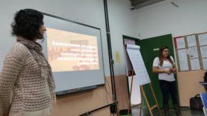 Duas mulheres estão diante de uma sala cheia de educadores.