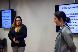 Duas mulheres em uma apresentação, diante de dois telões, em uma sala cheia de educadores.