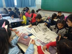 Sala de aula repleta de estudantes do 3º ano. Eles leem jornais em suas carteiras.