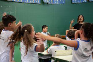 Aluno canta segurando microfone diante de toda classe, ao lado da professora. Os colegas danças com as mãos para cima.