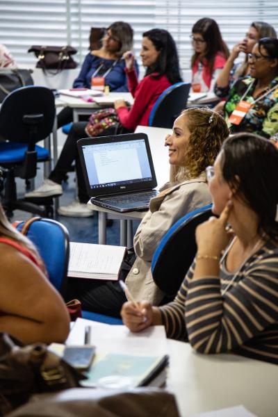Grupo de cerca de 15 educadores presta atenção a aula. Eles estão sentados em carteiras arranjadas em conjuntos e usam notebooks e cadernos sobre as mesas.