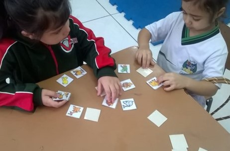 Sophia e uma amiga da mesma idade jogam um jogo de memória em uma sala de aula.