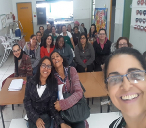 Grupo com cerca de 20 mulheres adultas posa para foto dentro de uma sala de aula.