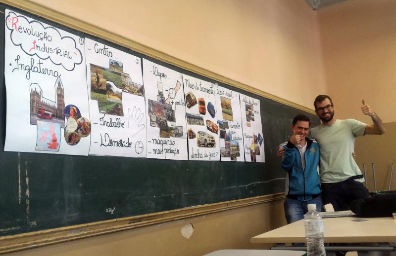Guilherme e seu professor se abraçam e sorriem para foto ao lado do painel visual com ilustrações sobre a Revolução Industrial preparado pelo estudante.