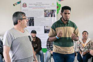 Um adolescente surdo faz sinais em Libras no centro de uma roda formada por seus colegas de classe. Ao seu lado, o intérprete faz a tradução do que está sendo dito.