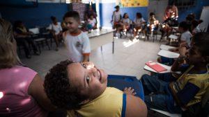 Em uma sala de aula, as crianças estão sentadas em círculo. No centro, a professora arruma o material pedagógico. Um garoto com Síndrome de Down sorri para a foto.