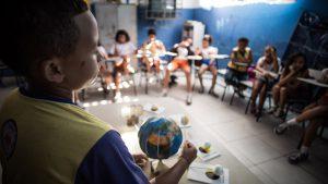 Cerca de 10 alunos estão sentados em semi-círculo em suas carteiras em uma sala de aula. Ao centro, um dos estudantes manipula uma reprodução do sistema solar feito com bolas de isopor e cartolinas.