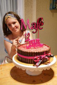 Mafê posa para foto atrás de bolo de aniversário
