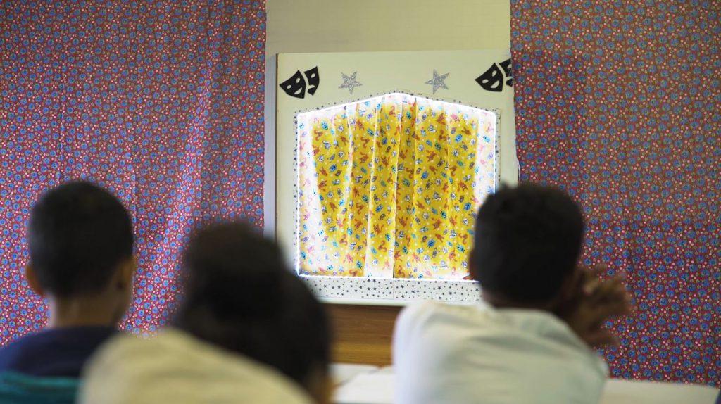 Três estudantes de costas observam material teatro de fantoches ao fundo. Fim da descrição.