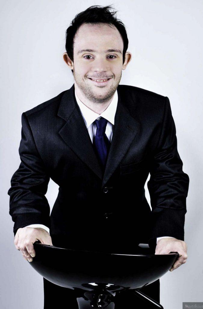 Samuel posa para foto de terno e sorridente. Seus braços estão apontados em uma banqueta a sua frente. Fim da descrição