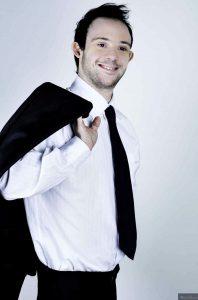 Samuel Sestato posa para foto segurando terno sobre o ombro. Fim da descrição.
