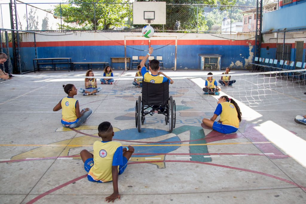 Crianças jogam vôlei sentados na quadra. Ao centro, um menino em cadeira de rodas, se prepara para rebater a bola que chega até ele. Fim da descrição.