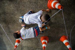 Dois meninos engatinham lado a lado em sentidos opostos sob uma trama de barbantes amarrados no topo de cones.