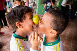 Dois meninos dançam com uma laranja equilibrada entre seus bochechas. Fim da descrição