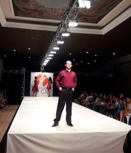 Samuel desfila em passarela de evento de moda. Do seu lado esquerdo, plateia assiste ao desfile. Fim da descrição.